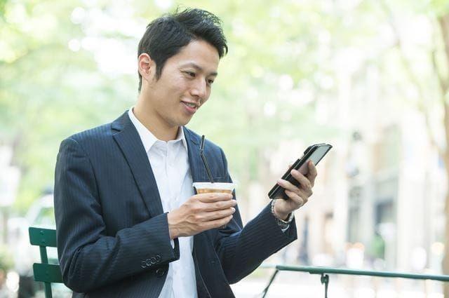 コーヒーを飲みながら携帯をチェックする男性