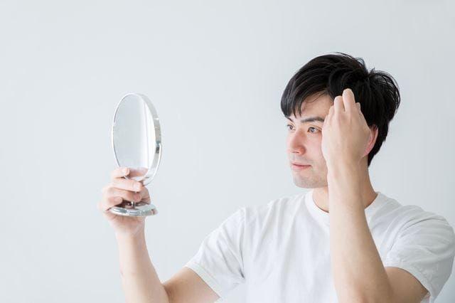 鏡で髪をチェックする男性