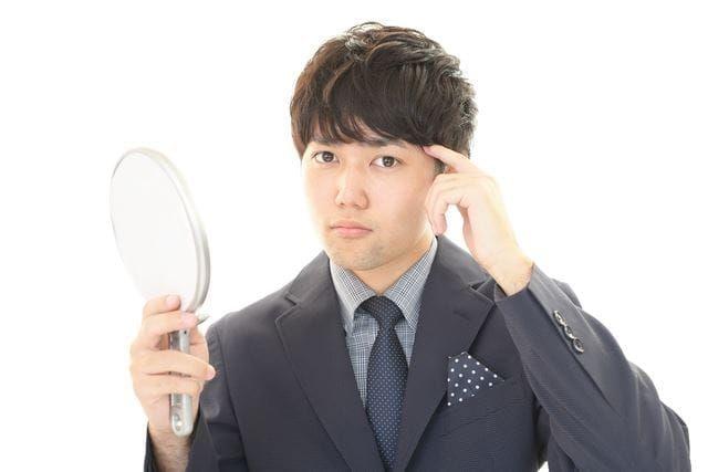 髪を気にする若い男性